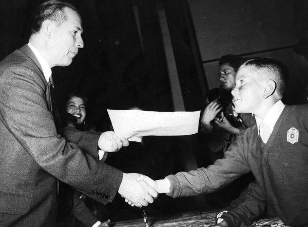 El alcalde Carlos Andrade Marín le entrega el diploma de sexto grado en 1959.