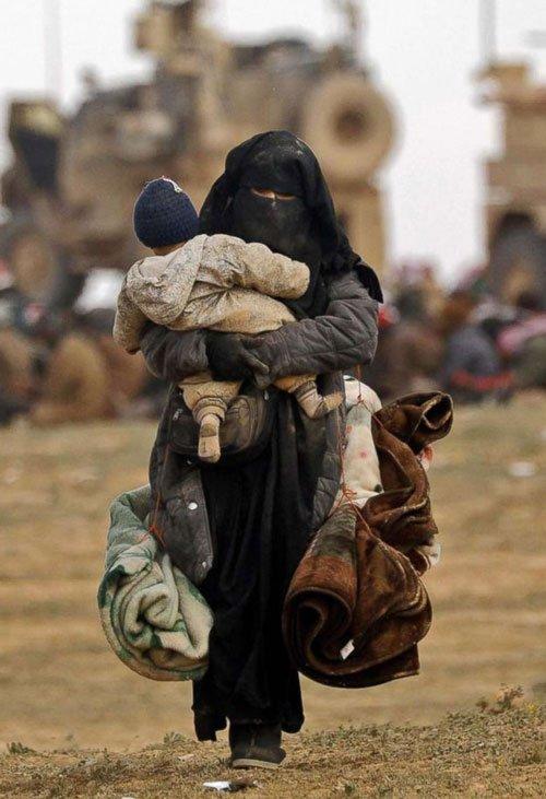 Mujeres con sus hijos llegan al campo de desplazados huyendo de los combates en Baguz, último bastión del Estado Islámico en Siria.